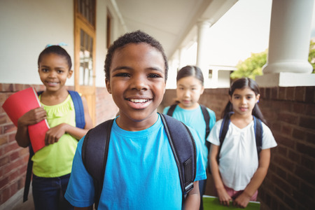 pupils: Portrait of cute pupils holding notebooks at corridor in school Stock Photo
