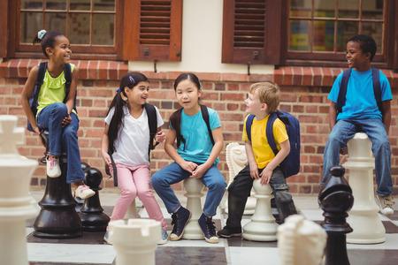 ajedrez: Alumnos felices que se sientan en piezas de ajedrez gigantes en la escuela
