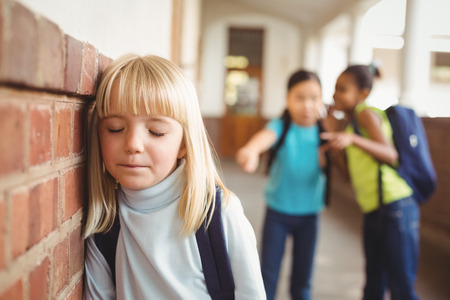 classmates: Sad pupil being bullied by classmates at corridor in school Stock Photo