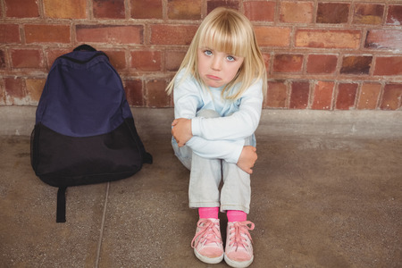 lonesomeness: Portrait of sad pupil sitting alone on ground at corridor