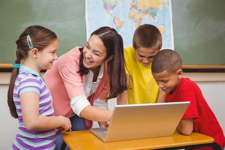 profesores: Los estudiantes y los maestros usan una computadora portátil en la escuela primaria Foto de archivo