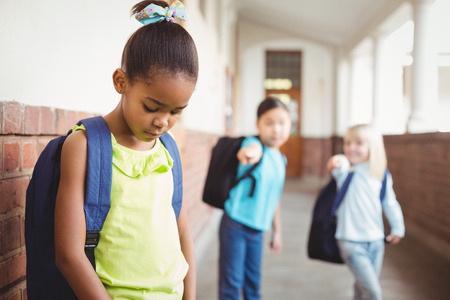 bullying: Sad pupil being bullied by classmates at corridor in school Stock Photo