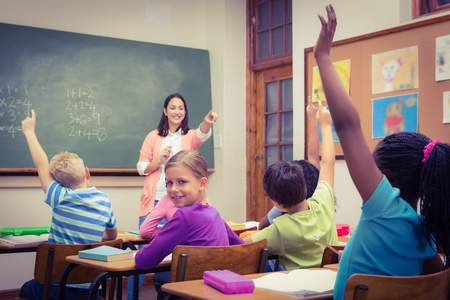 teaching adult: Teacher gettting an answer from a student at the elementary school