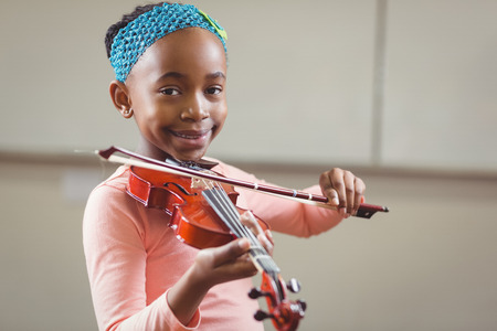 ni�os jugando: Portrait of smiling pupil playing violin in a classroom in school