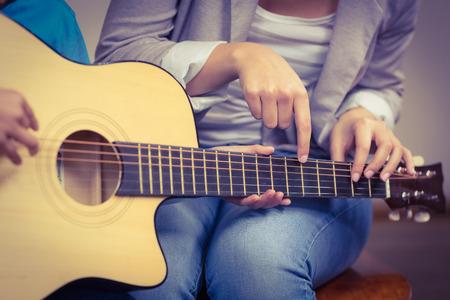 guitarra: Maestro dando clases de guitarra por alumno en un aula