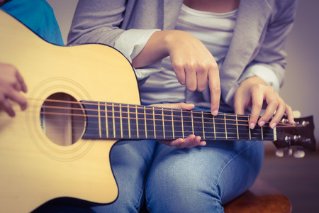 female teacher: Teacher giving guitar lessons to pupil in a classroom