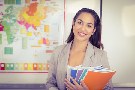 world of work: Portrait of pretty teacher holding notepads in a classroom in school Stock Photo