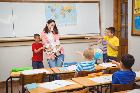 Students tying the teacher up at the elementary school Stock Photo