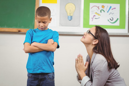 begging: Pretty teacher begging pupil for something in a classroom