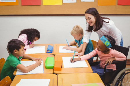 Happy teacher helping her students at the elementary school Stock Photo