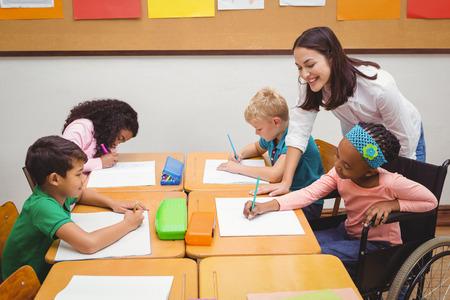 discapacidad: Profesor feliz ayudando a sus alumnos en la escuela primaria Foto de archivo
