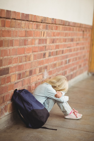 solitariness: Sad pupil sitting alone on ground at corridor Stock Photo