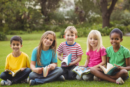 niños leyendo: Retrato de la sonrisa compañeros de clase que se sientan en la hierba y la celebración de libros en el campus