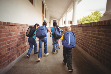 elementary school student: Rear view of pupils walking at corridor in school Stock Photo