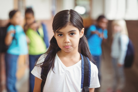 bullied: Portrait of sad pupil being bullied by classmates at corridor in school