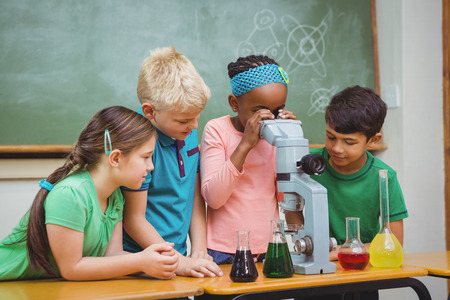 Students using science beakers and a microscope at the elementary school