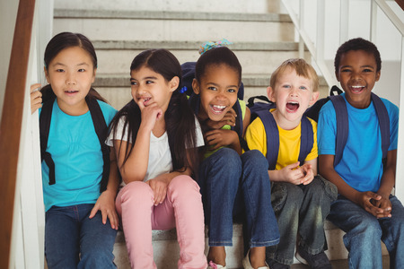 Portrait of happy pupils laughing and sitting on stairs in school Stock Photo