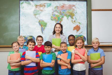 profesor alumno: Estudiantes que se colocan con el maestro en la escuela primaria