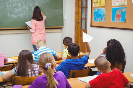 Student about to throw a paper airplane at the elementary school Stock Photo