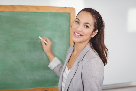 female teacher: Portrait of pretty teacher writing on chalkboard in a classroom in school