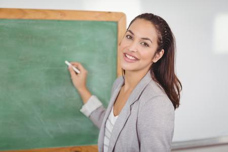 Portrait of pretty teacher writing on chalkboard in a classroom in school