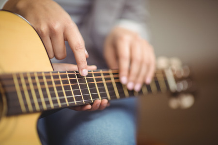 učit se: Učitel dává kytarové lekce na žáka ve třídě Reklamní fotografie