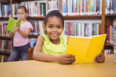 black children: Happy pupil reading a library book at the elementary school