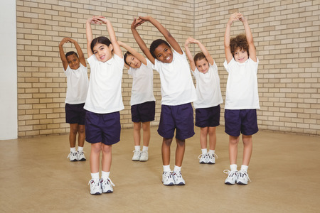 uniformes: Estudiantes felices estiramiento juntos en la escuela primaria Foto de archivo
