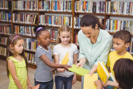 escuela primaria: Alumnos y profesor en la biblioteca de la escuela primaria