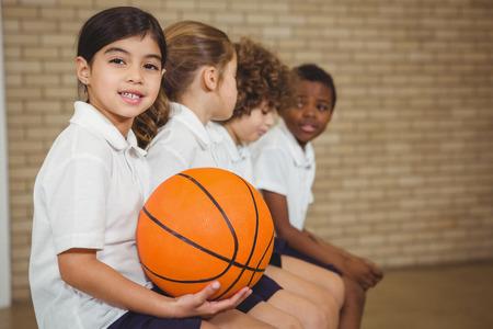 Die Schüler auf einem Sport Bank an der Grundschule sitzen