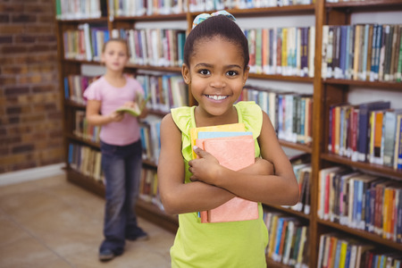 school library: Smiling student holding a few books at the elementary school