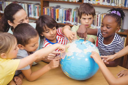world of work: Pupils and teacher looking at globe in library at the elementary school
