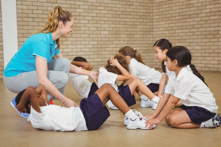 educacion fisica: Los estudiantes ayudan a otros estudiantes ejercitan en la escuela primaria