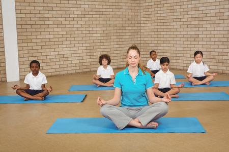 mujer meditando: Los estudiantes y profesores haciendo yoga plantean en la escuela primaria