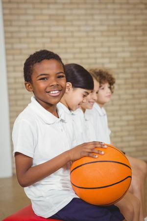 educacion fisica: Estudiante que sostiene el baloncesto con otros jugadores en la escuela primaria Foto de archivo