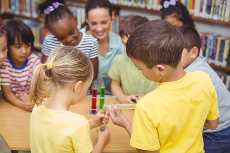 science lesson: Pupils and teacher doing science in library at the elementary school Stock Photo