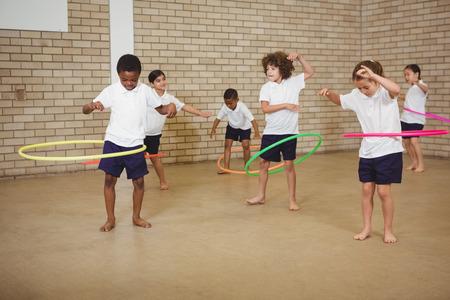 niñas jugando: Los estudiantes que usan algunos aros de hula en la escuela primaria