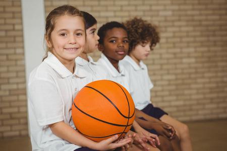 baloncesto chica: Estudiante que sostiene el baloncesto con otros jugadores en la escuela primaria Foto de archivo
