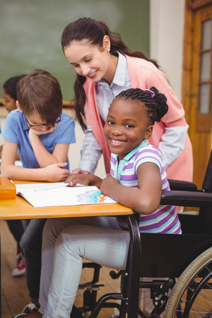 discapacidad: Disabled pupil smiling at camera in classroom at the elementary school
