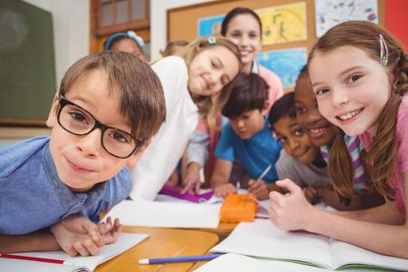 Lehrer und Schüler am Schreibtisch arbeitet gemeinsam an der Grundschule