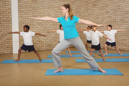 educacion fisica: Los estudiantes y profesores haciendo yoga plantean en la escuela primaria