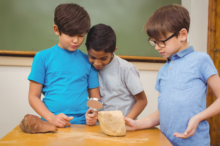 schoolkid search: Pupils looking at rock with magnifying glass at the elementary school