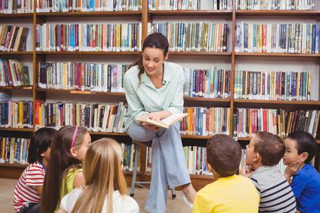 library: Profesor que lee a sus alumnos una historia en la escuela primaria Foto de archivo
