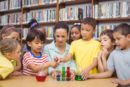 school work: Pupils and teacher doing science in library at the elementary school Stock Photo