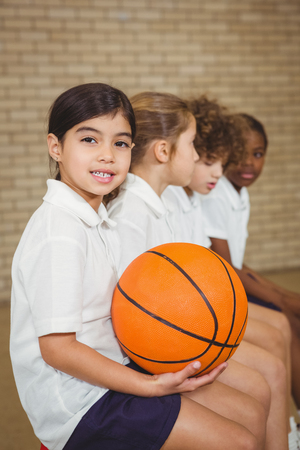 fellow: Student holding basketball with fellow players at the elementary school Stock Photo