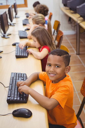 girls back to back: Smiling student using a computer at the elementary school