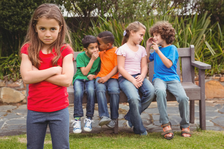 Upset child standing away from group sitting on a bench