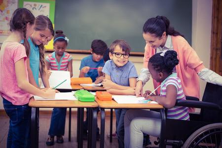 niños discapacitados: Los alumnos y los profesores que trabajan en el escritorio junto a la escuela primaria