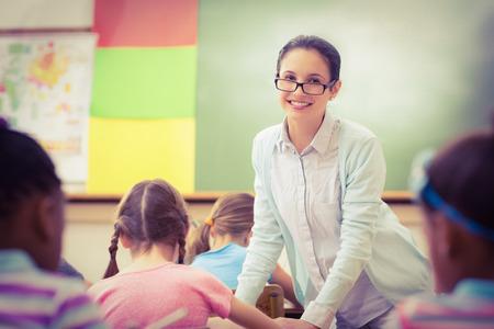 cheerful woman: Profesor de ayudar a un alumno durante la clase en la escuela primaria