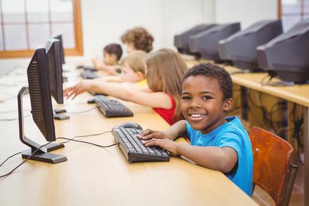 Estudiante sonriente que usa un ordenador en la escuela primaria